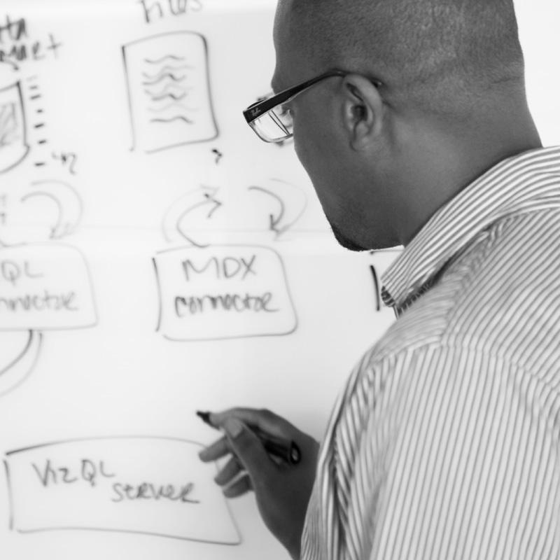 Homme examinant des données sur un tableau blanc
