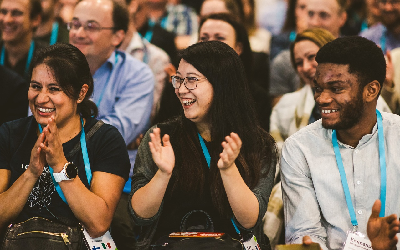 Two women and a man applaud with big smiles for a customer presentation at Tableau Conference Europe.