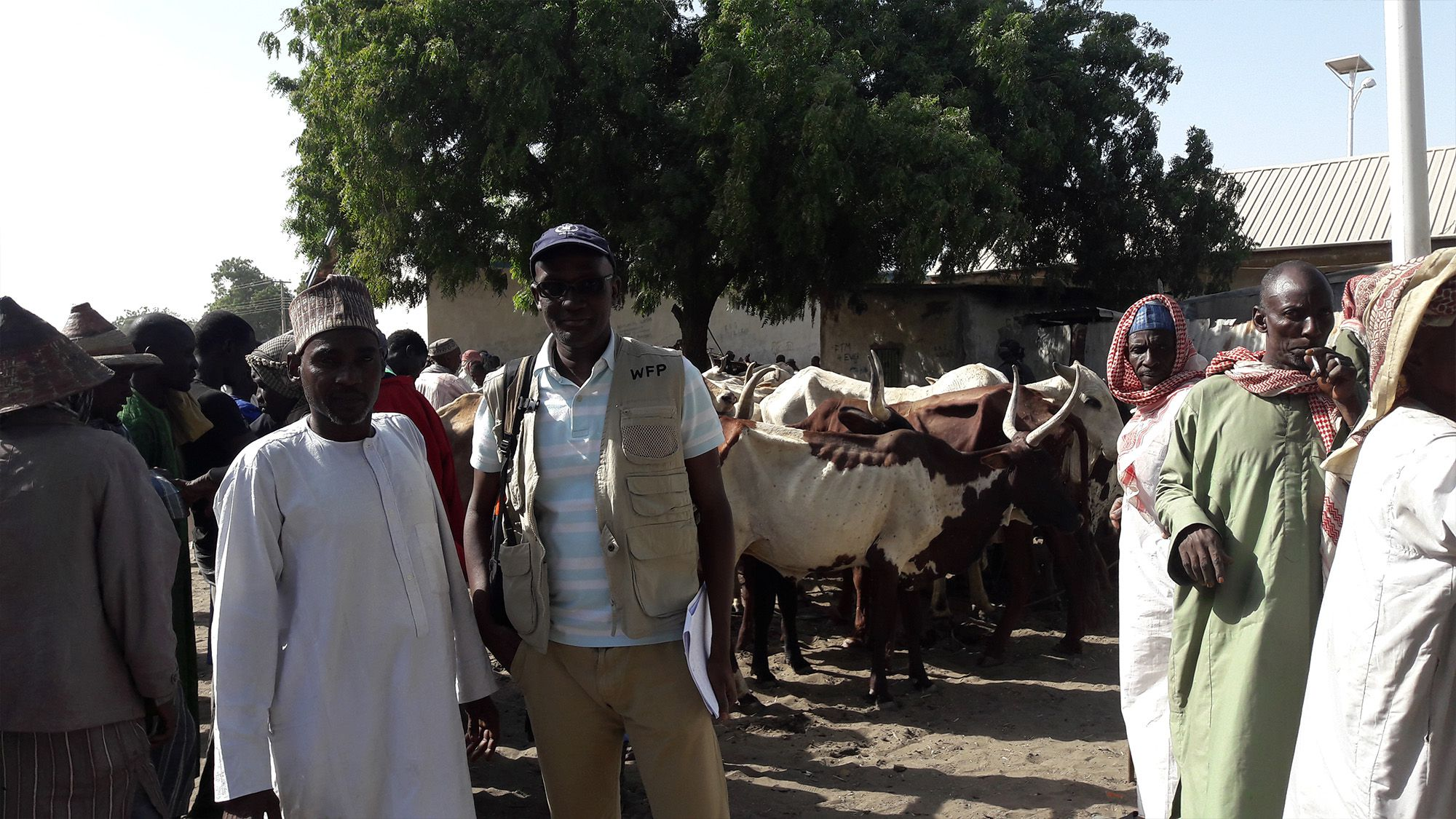 WFP's Moustapha Toure poses alongside a survey respondent at a cattle market outside Maiduguri, Nigeria. Photo Credit: WFP/Amadou Baraze